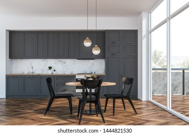 Interior of stylish kitchen with white and marble walls, wooden floor, gray countertops and cupboards, round dining table with black chairs and balcony with loft window. 3d rendering