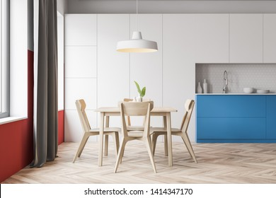 Interior of stylish kitchen with white and red walls, wooden floor, blue countertops with built in sink and white cupboards. Square dining table with chairs. 3d rendering