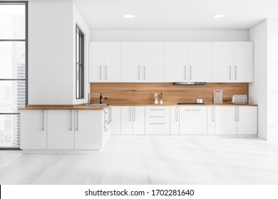Interior of stylish kitchen with white and wooden walls, wooden floor, white countertops with built in sink and cooker and cupboards. 3d rendering
