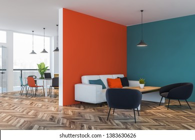 Interior of stylish living room with orange and blue walls, white sofa with colorful cushions near wooden coffee table with black armchairs. Dining room in background. 3d rendering
