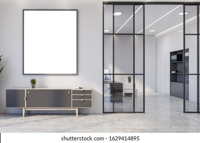 Interior of stylish living room with white walls, concrete floor, comfortable gray chest of drawers with vertical mock up poster frame above it and home office in background. 3d rendering