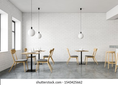 Interior of stylish loft restaurant with white brick walls, concrete floor, square tables with chairs, bar with wooden stools and modern lamps. 3d rendering