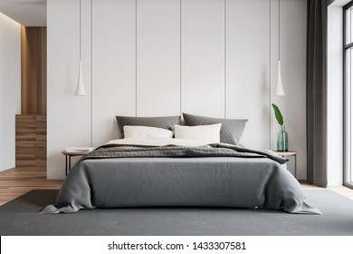 Interior of stylish master bedroom with white walls, wooden floor, double bed on gray carpet, two bedside tables with books and plant and wooden cabinet in background. 3d rendering