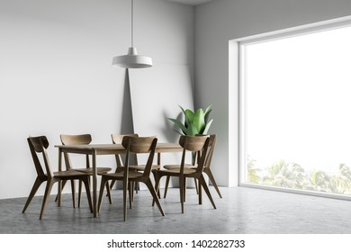 Interior of white dining room with concrete floor, wooden table with chairs and large window. Vertical poster in corner. 3d rendering