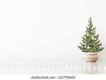 Interior white wall mock up with decorated christmas tree in basket and garland lights on empty background. 3D rendering.