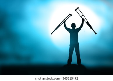 International Day of Persons with Disabilities (IDPD) concept: Silhouette  patient standing up and raising his crutches at blurred night background