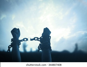 International day for the remembrance of the slave trade and its abolition concept: Silhouette human hands raising and broken chains at night background