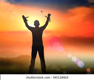 International day for the remembrance of the slave trade and its abolition concept: Silhouette human hand broken chains with bird flying against twilight sky