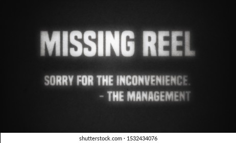 An intertitle from a fake silent film, projected over an old theater screen (vintage style, old lamp, dust and hair): missing reel; sorry for the inconvenience; the management. Black and white.