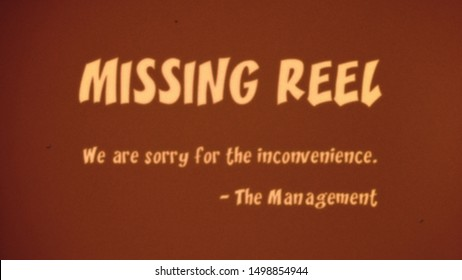 An intertitle projected over an old theater screen (vintage film style with dust and hair): missing reel; we are sorry for the inconvenience; the management. 1970s retro colors, funny font.