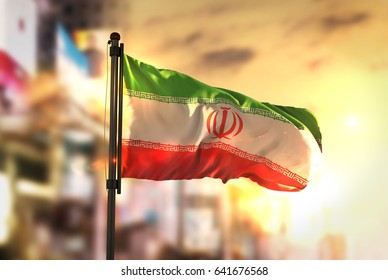 Iran Flag Against City Blurred Background At Sunrise Backlight 3D Rendering