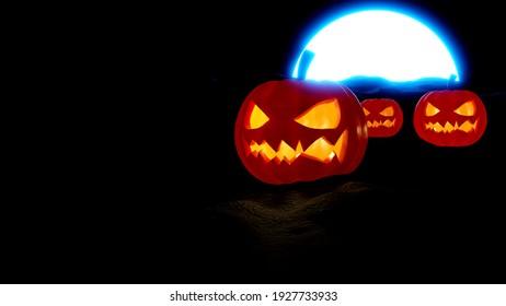 Jack O lanterns Halloween citrouille face effrayante avec la lumière orange sur terre sombre et la nuit de la lune bleue rendu 3D avec l'espace de copie