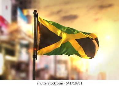 Jamaica Flag Against City Blurred Background At Sunrise Backlight 3D Rendering