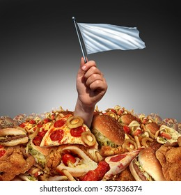 Junk food surrender and giving up fatty food or quitting a high fat lifestyle and dieting help concept as a hand holding a white flag drowning in a heap of greasy snacks.