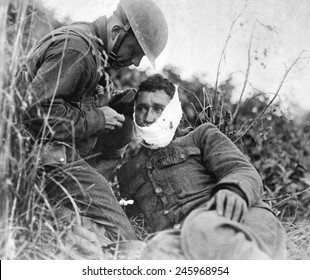 A just wounded American soldier, receiving first-aid treatment from a comrade. WWI. Varennes-en-Argonne, France. Sept. 26, 1918