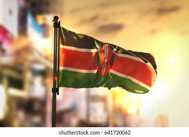 Kenya Flag Against City Blurred Background At Sunrise Backlight 3D Rendering
