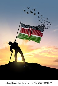 Kenya flag turn to birds while being planted by a man on a hill during sunrise.