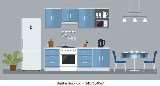 Kitchen in a blue color. There is a furniture, a stove, a refrigerator, a microwave, a kettle and other objects in the picture. There is also a table and chairs in the image. Raster