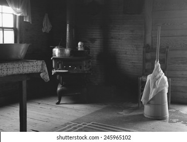Kitchen in the home of tobacco sharecropper. It could be a 19th century kitchen with a cast iron cooking stove, wash basin, and a butter churn. North Carolina. July 1939 photo by Dorothea Lange.