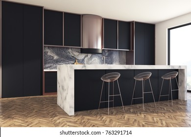 Kitchen interior with a wooden floor, black countertops and cupboards with built in appliances. A marble bar stand with round stools in the foreground. Side view. 3d rendering mock up