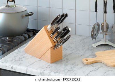 Kitchen knives with wooden block on the kitchen desk, 3D rendering