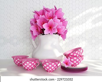 Kitchen still life. Ceramic vase with pink flowers and tea cups on the table in front of white till wall.