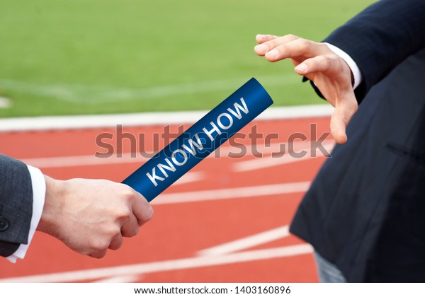 Know How - Hands of Businessman Passing Relay Baton in outside in stadium on running track - Concept Knowledge