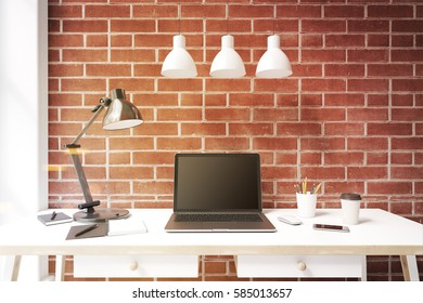 Laptop with a black screen is standing on a white desk in an office with brick walls and three ceiling lamps. 3d rendering, mock up, toned image