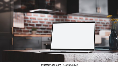 Laptop with a blank screen on a wooden table on the background of a loft kitchen - 3d rendering