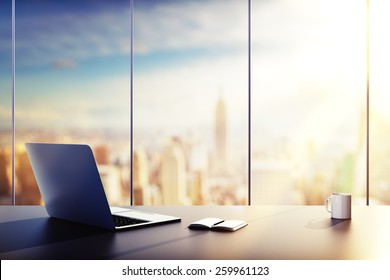 laptop, cup and diary on table in office at sunrise - Shutterstock ID 259961123
