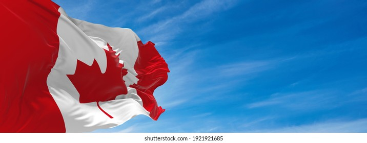 Large flag of canada  waving in the wind against the sky with clouds on sunny day. 3d illustration