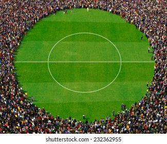 Large group of people seen from above, gathered around a circle, standing on football field background