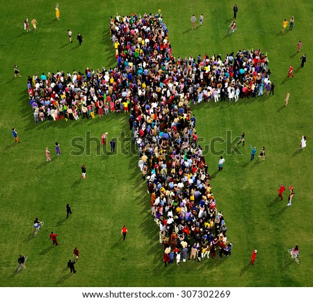 Large group of people seen from above gathered together in the shape of  a cross, on a grass background