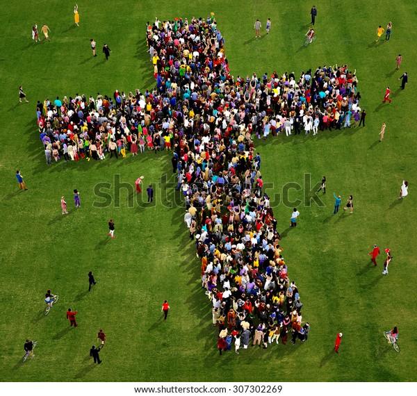 Große Gruppe von Menschen, die von oben gesehen wurden, versammelt in Form eines Kreuzes auf grasem Hintergrund