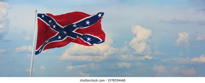 Large rebel flag waving in the wind . the Confederate battle or Dixie flag. Stars and Bars. Vintage United States flag. panoramic view with copy space for wide banner. 3d illustration