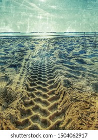 Large truck tire tracks in sand on the seashore,Large truck tire tracks in sand,traces of tractor tires in a large mud, Rural muddy road after rain, etched traces in the mud,autumn