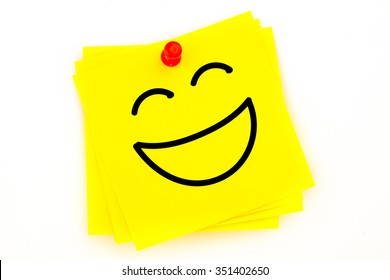 Laughing face against sticky note with red pushpin