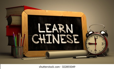 Learn Chinese - Chalkboard with Hand Drawn Text, Stack of Books, Alarm Clock and Rolls of Paper on Blurred Background. Motivational Quote. Toned Image.