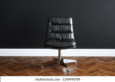 Leather office chair in black interior with wooden parquet floor 3D render