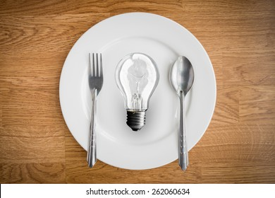 Light bulb in plate and fork and spoon on wooden table. brain food  Idea concept