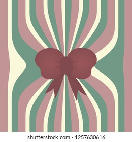 Light burgundy, green and cream christmas wrapping paper background with a burgundy bow.