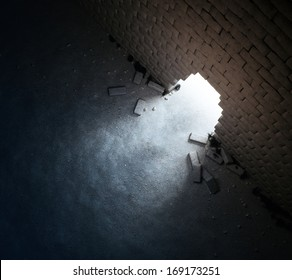 Light rays shining out of an opening in a brick wall