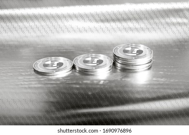 Litecoin (LTC) digital crypto currency. Stack of silver coins against the background of numbers. Cyber money. 3D Render.