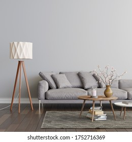 Living room interior with grey sofa, two coffee tables on the carpet and the floor lamp. Empty gray wall mockup. A pile of books on the carpet, a candle and flowers on the table. 3D render.