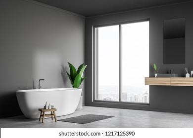 Loft bathroom corner with gray walls, concrete floor, white bathtub and sink with vertical mirror. 3d rendering