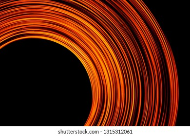Long exposure motion glow. Orange neon light lines swirl. Round abstract circle shape with black empty copy space inside.