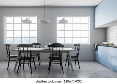Long white table with black chairs standing around it in a white kitchen with blue countertops and concrete floor. Big windows. 3d rendering