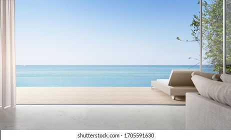 Lounge chair on terrace near bright living room and sofa in modern beach house or luxury pool villa. Cozy home interior 3d rendering with sea view.