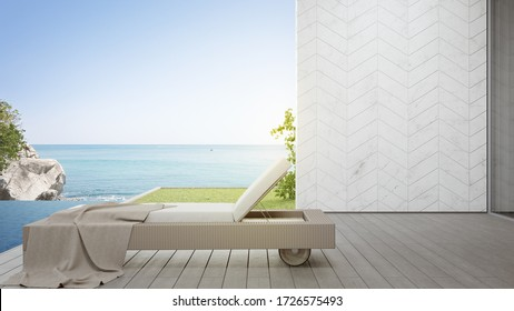 Lounge chair on terrace near swimming pool and garden in modern beach house or luxury villa. Wooden deck 3d rendering with sea view.
