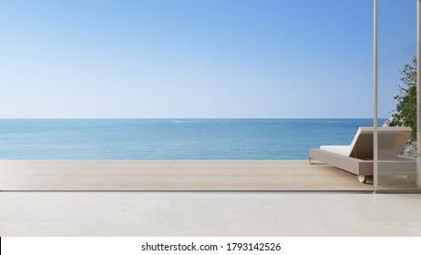 Lounge chair on terrace near living room in modern beach house or luxury villa. Cozy home interior 3d rendering with sea view.